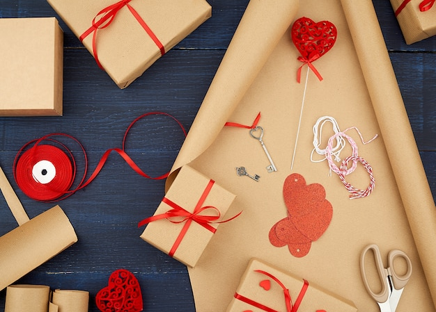 Brown kraft paper, packed gift bags and tied with a red ribbon, red heart