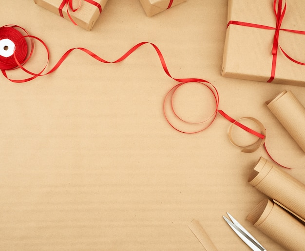 Brown kraft paper, packed gift bags and tied with a red ribbon, set of items