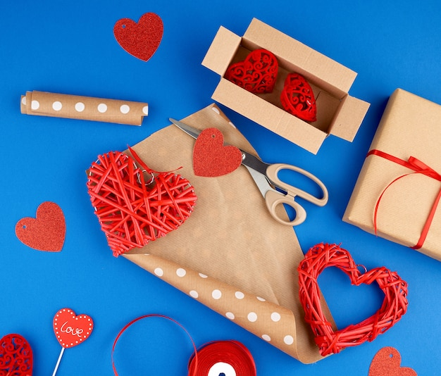 Brown kraft paper, packed gift box, red ribbon, red heart, set of items for making gifts.
