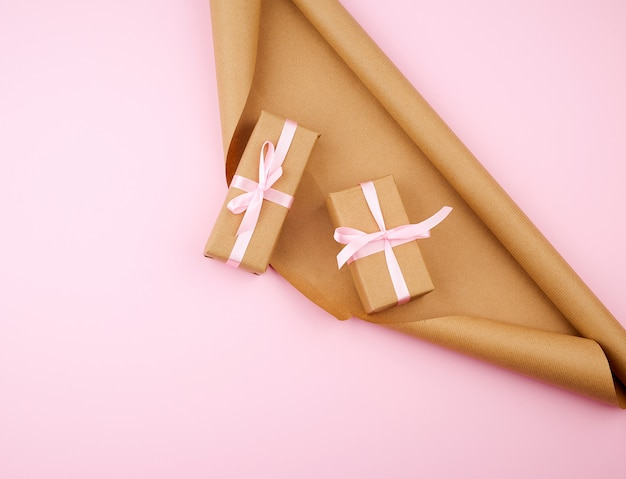 Brown kraft paper, packed gift boxes and tied with a pink ribbon