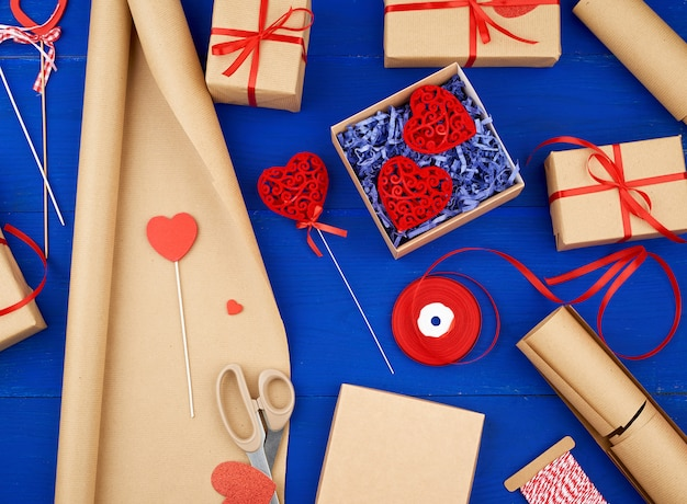 Brown kraft paper, packed gift boxes and tied with a red ribbon, red heart, set of items for making gifts