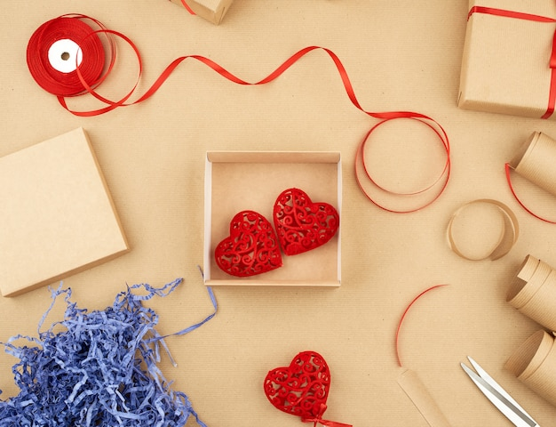 Brown kraft paper, packed gift boxes and tied with a red ribbon, red heart