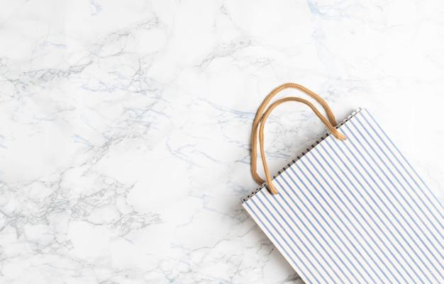 Коричневая сумка для покупок из крафт-бумаги на белом мраморном фоне