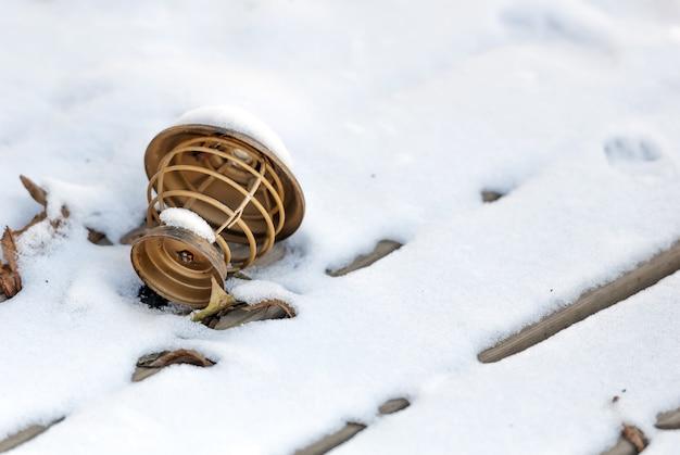 Lampada marrone di legno lanciata sulla neve accanto a una foglia in inverno