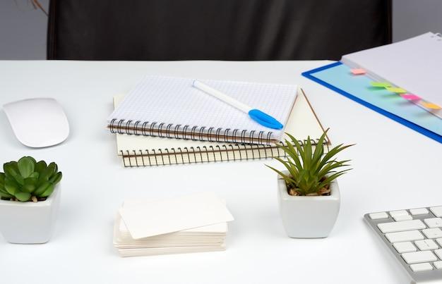 茶色の革張りのアームチェアと白いテーブルに文房具、紙のノート