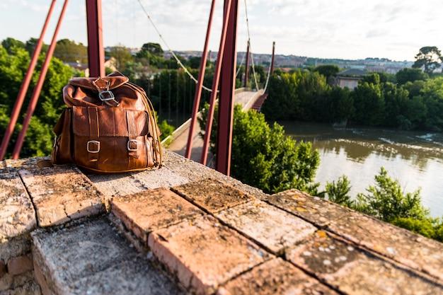 Коричневый кожаный рюкзак и красный мост. концепция образа жизни и свобода.