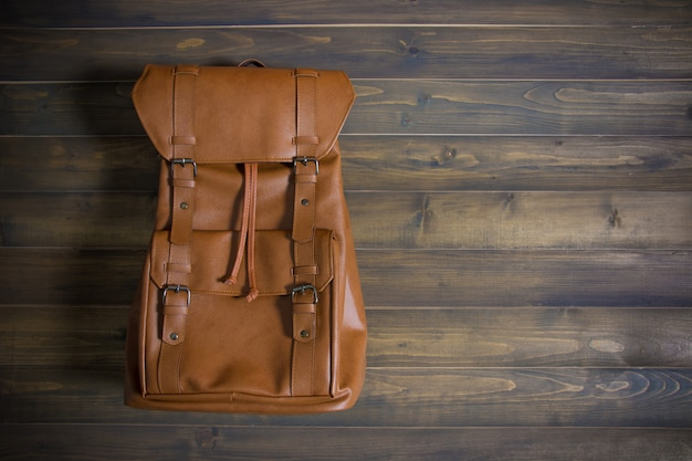 Brown leather bag on wooden table. top view. travel concept.
