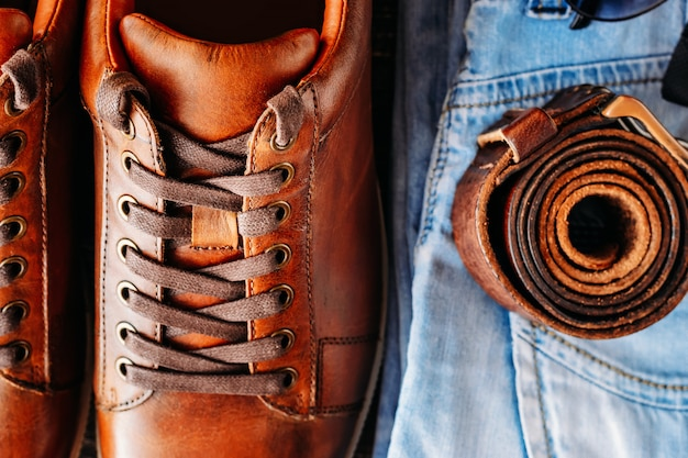 Brown leather casual shoes, jeans and belt top view close up. fashion concept