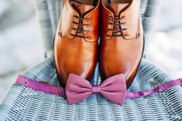Коричневые кожаные туфли жениха и развязанный галстук-бабочка.