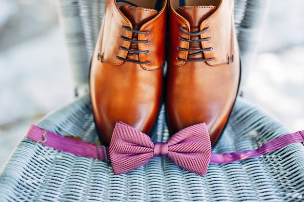 Brown leather groom shoes and an untied bow tie.