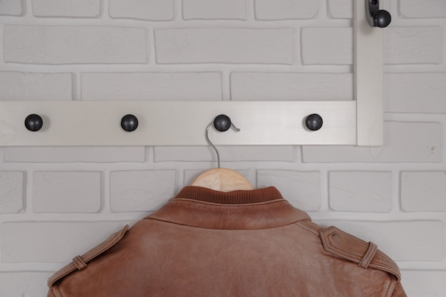 Brown leather jacket hanged on white wall hanger.