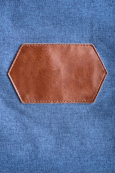 Brown leather label with stitching on denim. copy space. mockup