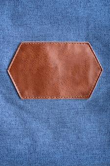Ярлык из коричневой кожи с отстрочкой на джинсовой ткани. скопируйте пространство. макет