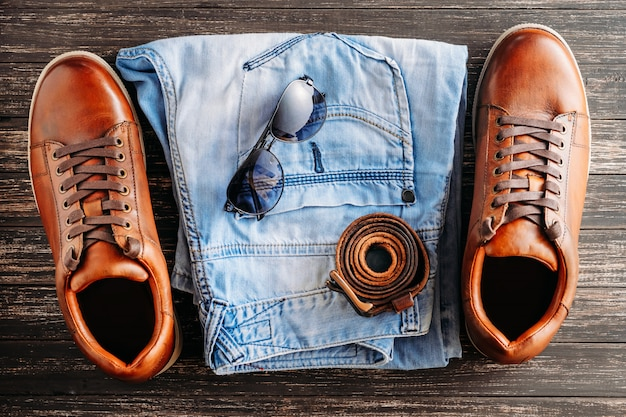 Brown leather men's boots, belt, sunglasses and blue jeans