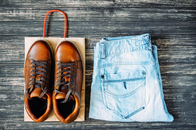 Brown leather men's boots and jeans on a wooden background, top view