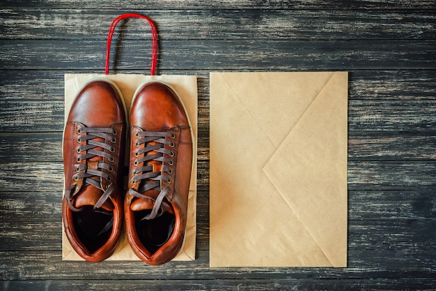 Brown leather men's boots and kraft envelope on a wooden background, top view