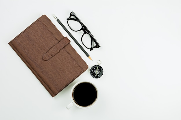 Brown leather notebook  and a coffee cup on white desk background