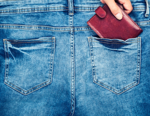 Brown leather purse lies in the back pocket of blue jeans