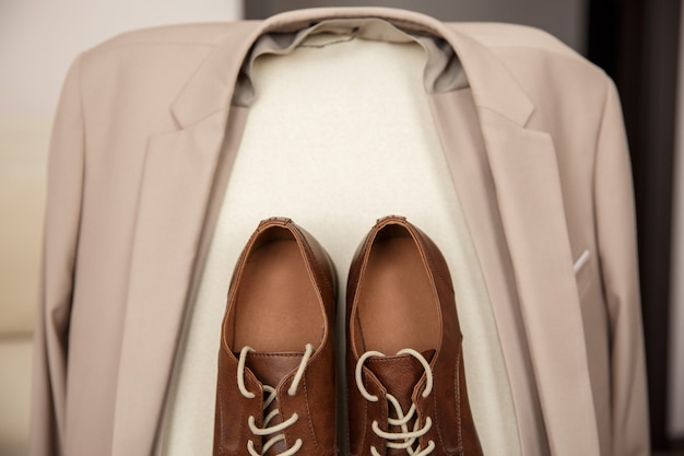 茶色の革の靴とベージュのスーツまたはジャケット