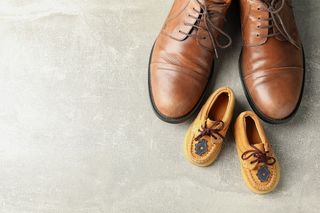 Brown leather shoes and children's shoes on grey background