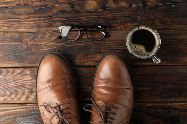 茶色の革の靴、一杯のコーヒー、木製の背景にメガネ