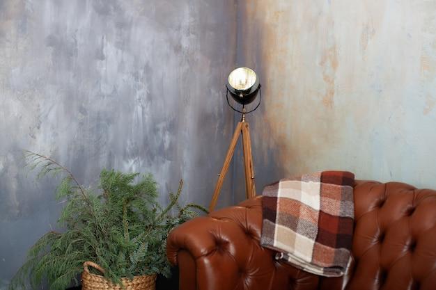 ダークロフトのインテリアに茶色の革張りのソファ。