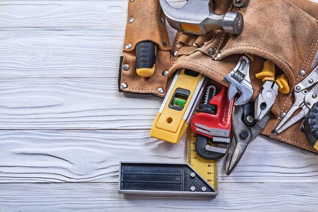 Коричневый кожаный пояс для инструментов со строительными принадлежностями на деревянной доске