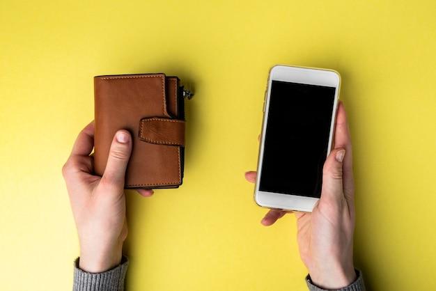 노란색 배경에 갈색 가죽 지갑과 휴대폰.