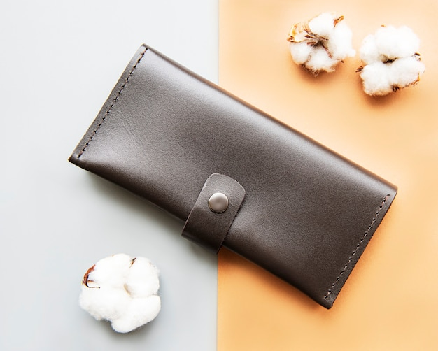 Brown leather wallet with cotton flowers on a grey and brown surface