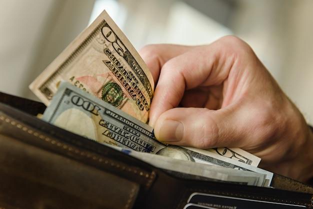 손에 달러와 갈색 가죽 지갑입니다. 확대.