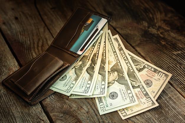 古い木の表面にドルが付いている茶色の革の財布。閉じる。