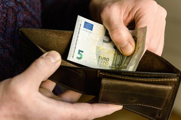 手にユーロを持った茶色の革の財布。閉じる。
