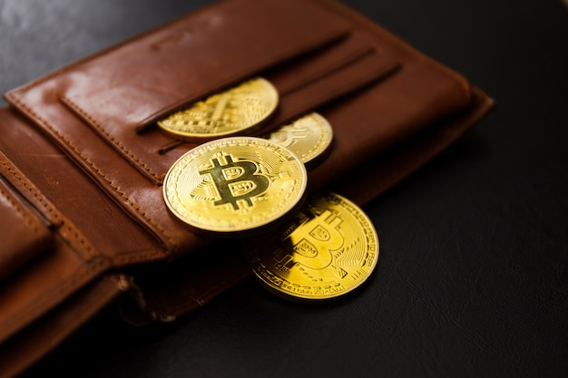 Brown leather wallet with metal bitcoins on black background.
