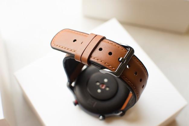 白い箱にスマートウォッチの茶色の革の時計ストラップ