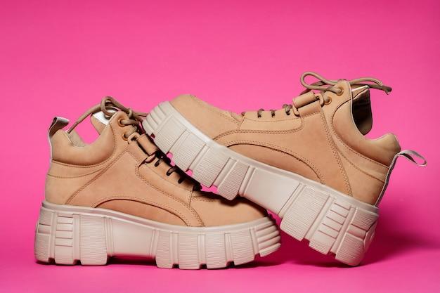Коричневая кожаная женская обувь с высокой подошвой на розовом фоне. модная обувь