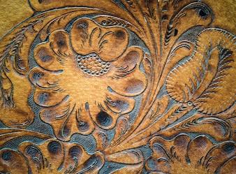 Brown leatherwork carved detail on saddle. Retro and vintage background.