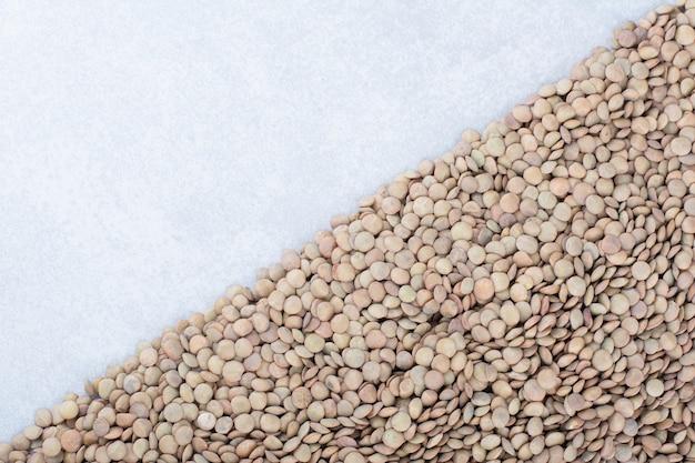 大理石の表面に三角形の山に配置された茶色のレンズ豆