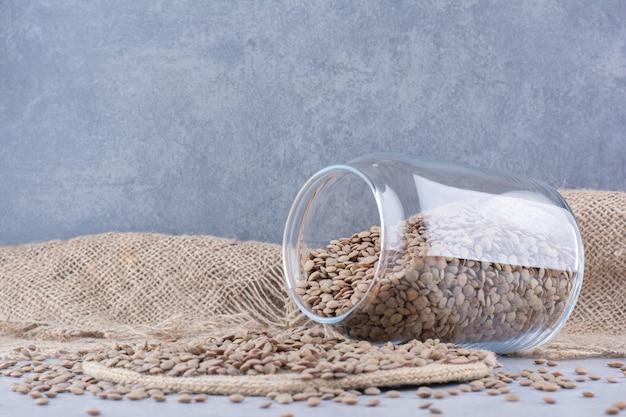 大理石の表面のトリベットの瓶から注ぐ茶色のレンズ豆