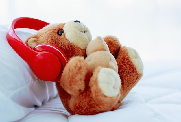 낭만적인 침대에 장식된 빨간 이어폰을 창의적으로 착용한 갈색의 사랑스러운 푹신한 곰 인형은 음악에 즐거워 보이며 행복한 휴가를 즐겁게 보내고 휴식을 취합니다.