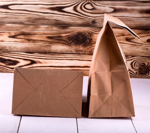 Brown lunch bag on white wooden table