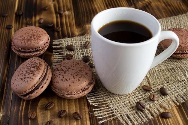 木製の素朴な背景に茶色のマカロンとコーヒー