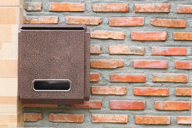 Brown mailbox on brick wall.