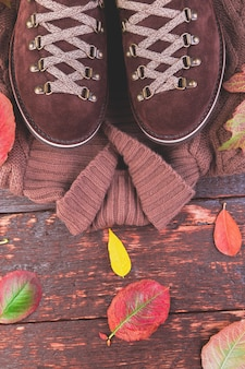 Brown man suede boots with sweater on wooden with leaves. autumn or winter shoes. outfit.