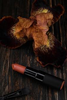 Коричневая матовая помада и цветок ириса на деревянном столе косметика модного гламурного цвета
