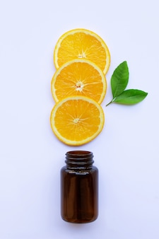 Brown medicine glass bottle with orange fruit  slices and green leaves on white