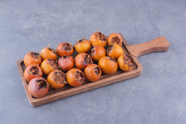 Brown medlars in a wooden platter on blue surface Free Photo