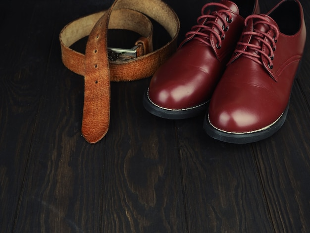 Brown men's boots, jeans and belt on wooden.