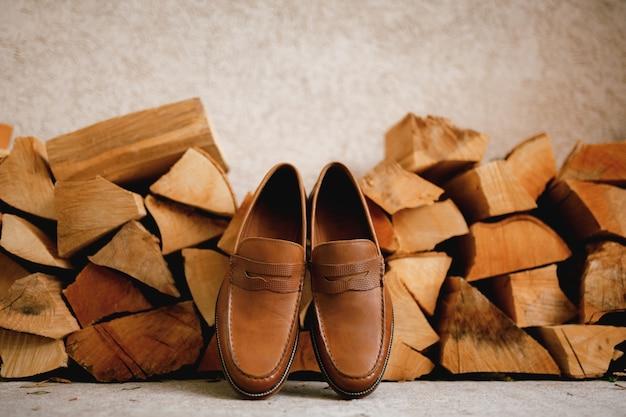 木の丸太の横にある茶色の紳士靴