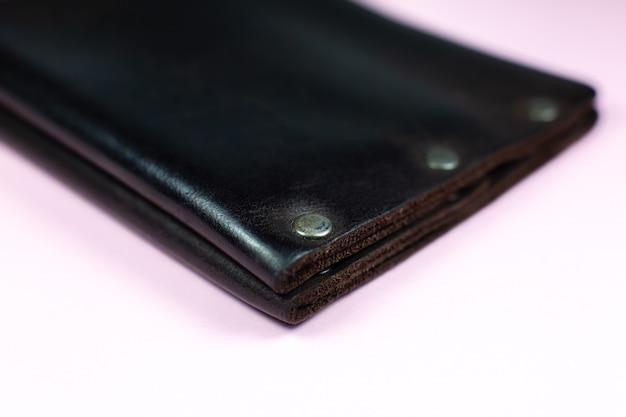 Коричневый мужской кожаный кошелек на розовом фоне.