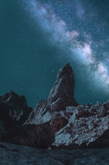 Brown monolith under teal and gray milky way
